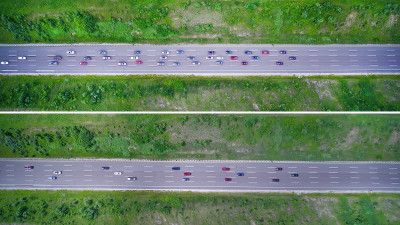 An overhead view of two demonstrations conducted by Ford Motor Company and Vanderbilt University traffic researchers. In the top frame, 36 vehicles are spread evenly across three lanes and driving at 60 miles per hour before the lead vehicles brake to 40 miles an hour, causing a traffic backup. In the lower frame, a similar scenario, but all vehicles are using Ford's adaptive cruise control technology, which can automatically slow down and speed to keep pace with the car in front without getting fatigued or distracted. This scenario resulted in improved traffic flow.