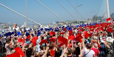 Жители Владивостока выстраиваются на Золотом мосту в форме Государственного Флага России